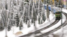 Le jouet de train de Noël passe par la forêt fantastique d'hiver dans le mouvement lent 3840x2160 banque de vidéos