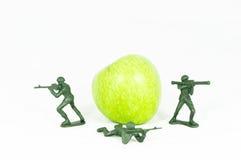 Le jouet de trois soldats protègent la pomme verte Image stock