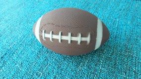 Le jouet du football sur la terre bleue Photo libre de droits
