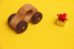 Le jouet en bois de voiture et le boîte-cadeau d'or avec le ruban rouge derrière sur le fond jaune diagonal ondulé, présentent po photo libre de droits