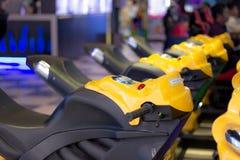 Le jouet jaune fait du vélo dans le terrain de jeu dans une ligne pour la simulation de emballage photo stock