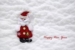 Le jouet mou de Noël sous forme de Santa Claus est situé dans la perspective de la neige naturelle blanche photos stock