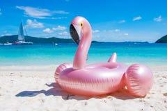 Le jouet rose gonflable géant de flotteur de piscine de flamant sur le tropical soit photos libres de droits