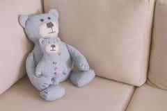 Le jouet soutient se reposer sur un sofa Image stock
