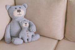 Le jouet soutient se reposer sur un sofa Photos libres de droits