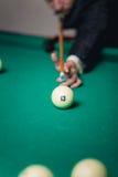Le joueur de billards frappe la boule Photo stock