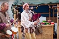 Le joueur de cornemuse et le batteur historiques se sont habillés dans des vêtements antiques Photos stock