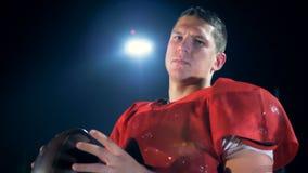 Le joueur de football américain déterminé tord la boule dans des ses mains banque de vidéos
