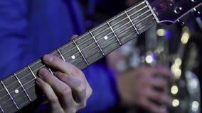 Le joueur de guitare dans l'équipement noir joue la guitare acoustique sur l'étape avec l'autre musicien banque de vidéos