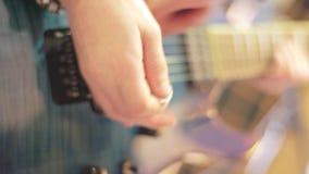 Le joueur de guitare emploie la sélection pour jouer les ficelles bleues de guitare électrique dans le studio musical banque de vidéos