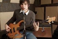 Le joueur de guitare est jouant et chantant dans le studio Photos stock