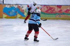 Le joueur de hockey tire le galet et les attaques image stock