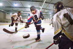 Le joueur de hockey tire le galet et attaque le gardien de but image stock