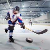 Le joueur de hockey tire le galet et attaque le gardien de but Photos libres de droits
