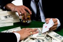 Le joueur de poker tenant le verre de whiskey et les as triples d'exposition Photos libres de droits