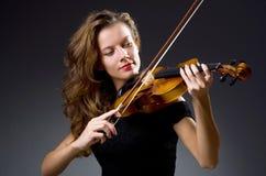 Le joueur musical féminin contre l'obscurité Image stock