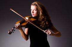 Le joueur musical féminin contre l'obscurité Photos stock