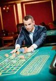 Le joueur poinçonne des piles des puces à la table de roulette Photos stock