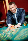 Le joueur poinçonne la pile des puces au casino Photographie stock libre de droits
