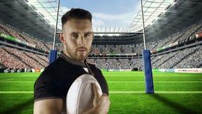 Le joueur sérieux de rugby tient la boule de rugby banque de vidéos