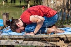 Le jour d'été de yoga de pratique en matière de jeune homme par l'enfant de lac pose pour la relaxation images stock