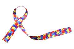 Le jour de conscience et de fierté d'autisme du monde avec le puzzle modèlent le ruban d'isolement sur le blanc Images libres de droits