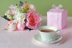 Le jour de mère fleurit avec le cadeau et la tasse de thé Photo libre de droits
