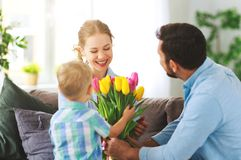 Le jour de mère heureux ! le père et l'enfant félicitent la mère en vacances image libre de droits
