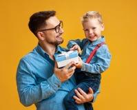 Le jour de p?re heureux ! papa mignon et fils ?treignant sur le fond jaune photographie stock