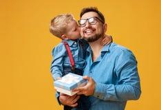 Le jour de p?re heureux ! papa mignon et fils ?treignant sur le fond jaune photo libre de droits