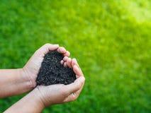 Le jour de terre, sauvent la terre, concept d'amour la main de femme tenant a Photographie stock