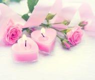 Le jour de Valentine Bougies et roses en forme de coeur roses Images stock