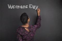 Le jour des femmes d'écriture de professeur de femme d'afro-américain sur le fond de conseil de noir de craie Photo libre de droits