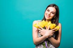 Le jour des femmes de printemps portrait de femme de sourire avec le bouquet des tulipes jaunes dans des mains d'isolement sur le photo stock