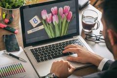 Le jour des femmes, le 8 mars sur un écran d'ordinateur Homme travaillant dans son bureau Images stock