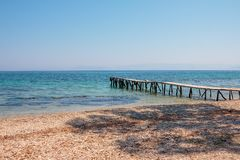 Le jour ensoleillé en bois d'eau de mer de turquoise de pilier, pierres échouent, île de la Grèce Endroit sauvage romantique Mer  Photo libre de droits