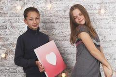 Le jour heureux de Valentine Jeune garçon donnant une image de coeur à son amie Photo libre de droits