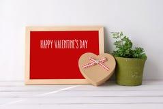 Le jour heureux du ` s de valentine sur le conseil en bois et le coeur forment le boîte-cadeau dessus Images stock