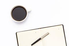 Le journal intime ouvert noir, stylo et une tasse de café noir sur le fond blanc Image libre de droits