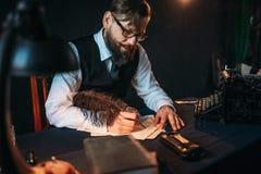 Le journaliste barbu en verres écrit avec la plume Photographie stock libre de droits