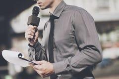Le journaliste parle dans le microphone, et tient le support pour les feuilles Image libre de droits