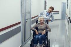 Le joyeux docteur pousse le fauteuil roulant avec le patient photo stock