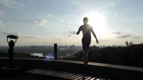 Le joyeux homme danse sur un mur de berge au coucher du soleil dans le ralenti banque de vidéos