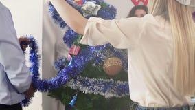 Le Joyeux Noël et bonnes fêtes de jeunes employés de bureau heureux décorent l'arbre de Noël dans le bureau Tir au ralenti banque de vidéos