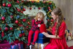 Le Joyeux Noël et bonnes fêtes la maman et la fille décorent l'arbre dans la chambre Famille affectueuse à l'intérieur photos libres de droits