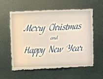Le Joyeux Noël et la bonne année textotent dans la couleur foncée sur le fond de papier de photo Photos stock