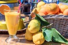 Le jus d'orange fraîchement serré dans une tasse en verre, à côté de la table se trouve des oranges et des citrons Photos stock