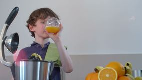Le jus d'orange frais fait maison de jeune garçon caucasien drôle dans la cuisine avec le presse-fruits électrique et le boivent banque de vidéos