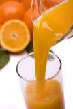 Le jus d'orange a plu à torrents dedans une glace Image stock