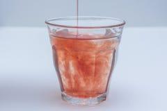 Le jus de fruit dilué a versé dans le verre de l'eau photo libre de droits